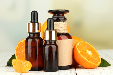 Tangerine essential oil and tangerines on wooden table Stock Photo