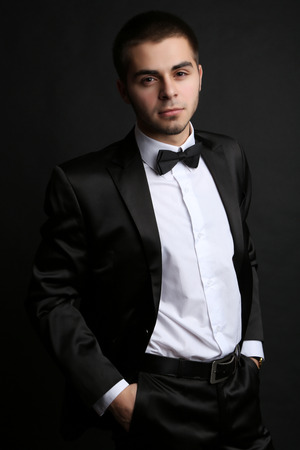 Handsome young man in suit on dark background Stock Photo - 26376048