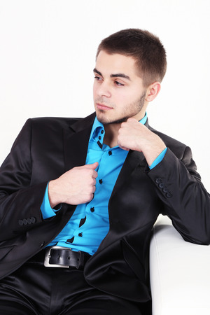 Handsome young man sitting on sofa on light background Stock Photo - 26376056
