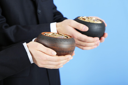 Two ceramic pots with golden coins in male and female hands, on color  photo