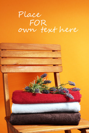 orange washcloth: Towels and flowers on wooden chair on orange
