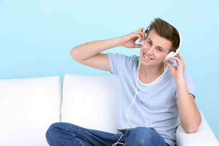 Guy sitting on sofa and  listening to music on blue background photo