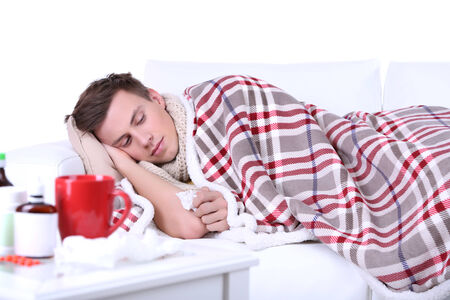 Guy wrapped in plaid lies on sofa is ill Stock Photo - 26376150