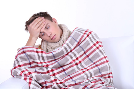 Guy wrapped in plaid sitting on sofa is ill Stock Photo - 26376151