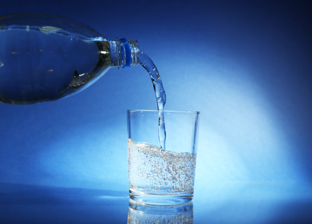 Pour water from bottle into  glass, on dark blue  photo