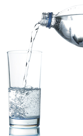 Pour water from bottle into  glass, isolated on white photo