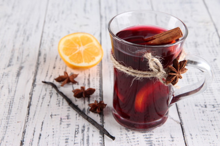 Mulled wine with lemon and spices on wooden  photo
