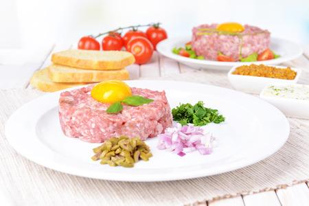 steak tartare: Delicious steak tartare with yolk on plate on table close-up