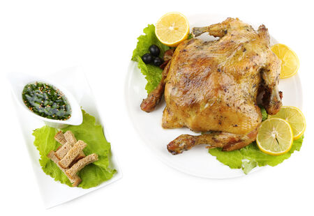 Whole roasted chicken with vegetables on plate, isolated on white photo