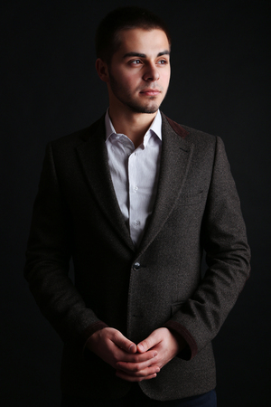 Handsome young man on dark background photo