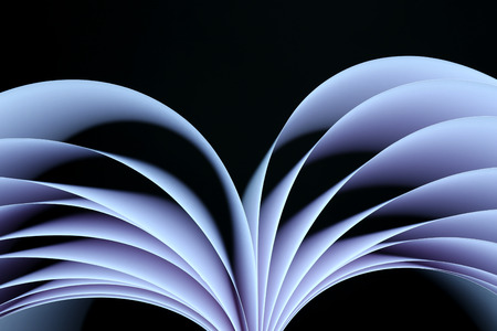 printed material: Abstract image of sheets white paper wave shape on black close-up