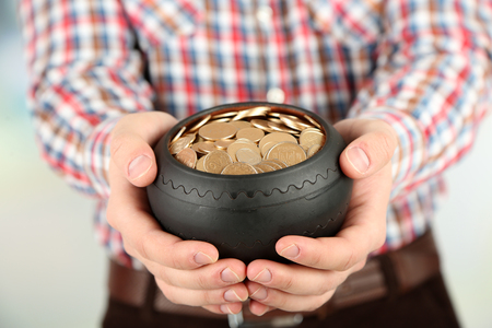 Ceramic pot with golden coins in male hands, on light  photo