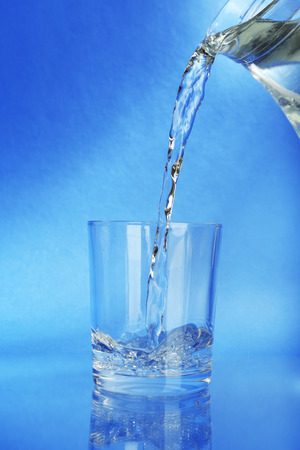 Pour water from  pitcher into  glass, on dark blue  photo