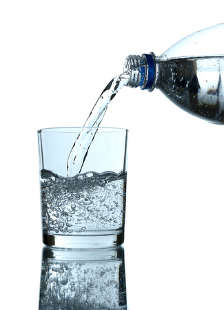 Pour water from bottle into  glass, on light blue  photo