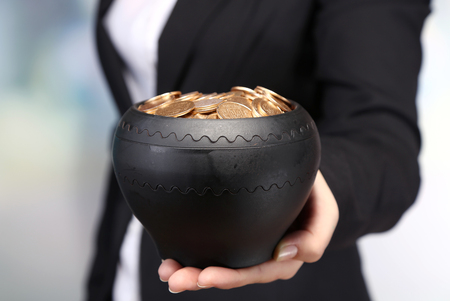 coin toss: Ceramic pot with golden coins in female hands