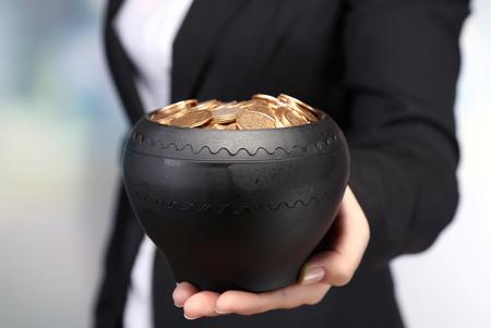 m�nzenwerfen: Keramik-Topf mit goldenen M�nzen in weiblichen H�nden