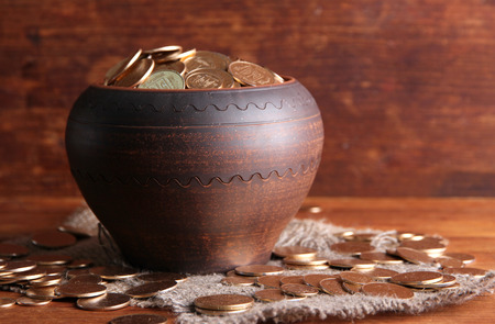Golden coins in ceramic pot, on wooden table  photo
