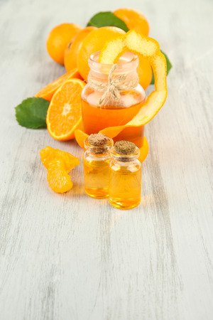Tangerine essential oil and tangerines on wooden table photo