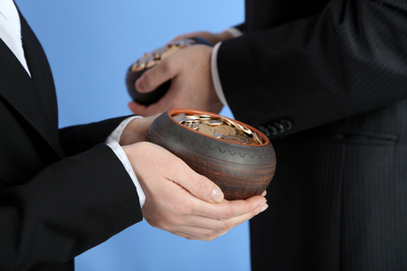 coin toss: Two ceramic pots with golden coins in male and female hands Stock Photo