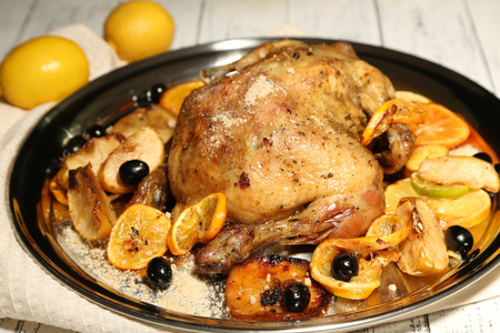 Whole roasted chicken with vegetables on tray, on wooden table Stock Photo - 26331033