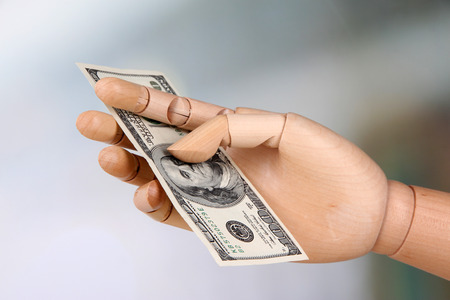 economise: Money in wooden hand, on light background