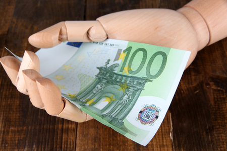economise: Money in wooden hand, on  color wooden table