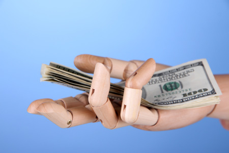 economise: Money in wooden hand, on color wall