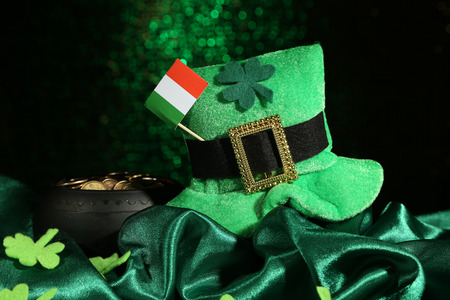 coins shot in golden color: Saint Patrick day hat, pot of gold coins and Irish flag on green shiny
