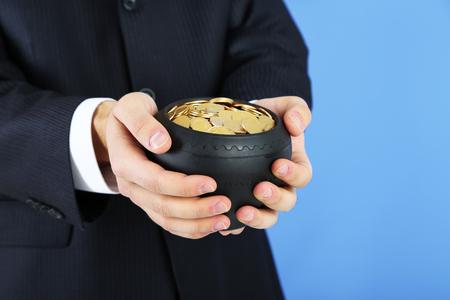 m�nzenwerfen: Keramik-Topf mit goldenen M�nzen in den m�nnlichen H�nden, auf farbigem Hintergrund