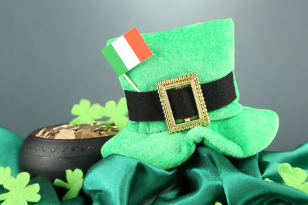 Saint Patrick day hat, pot of gold coins and Irish flag on grey background photo