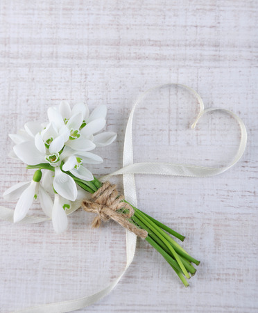 snow flowers: Bouquet of beautiful snowdrops on wooden background Stock Photo