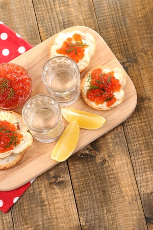 Red caviar in bowl and vodka on wooden board , on napkin on wooden background photo