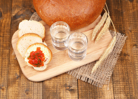 Composition with glasses of vodka  bread and red caviar on wooden table background photo