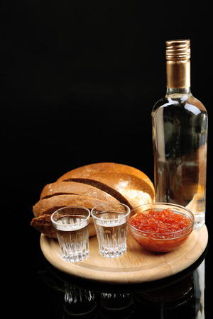 Bottle of vodka, red caviar, fresh bread on wooden board,  isolated on black photo