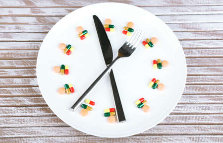 mealtime: Medication schedule and meals. Conceptual photo. On wooden background