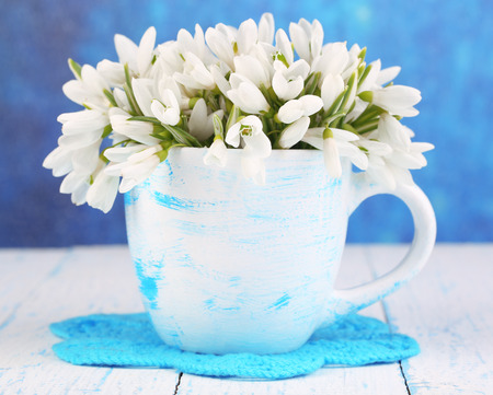 Beautiful snowdrops in vase, on wooden table on bright background photo