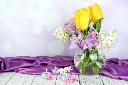 Flowers in vase with candles on table on bright background photo