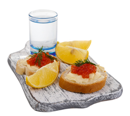 Sandwiches with caviar and vodka on wooden board isolated on white photo