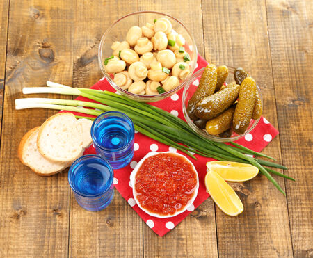 Composition with glass of vodka and marinated mushrooms, cucumbers on wooden background photo