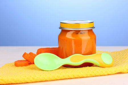 Jar of baby puree with spoon on napkin on blue background photo