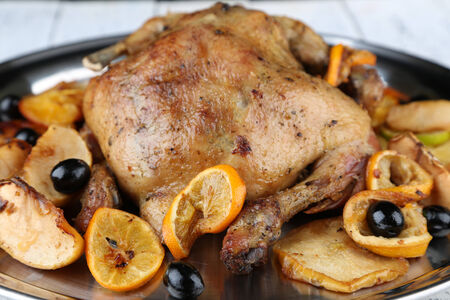 Whole roasted chicken with vegetables on tray, on wooden background photo