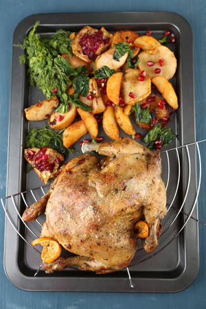 Whole roasted chicken with vegetables and fried potatoes on pan, on color wooden background photo