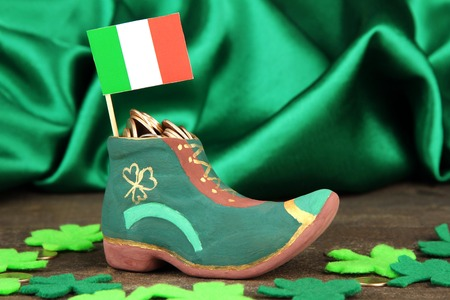 Saint Patrick day boot with gold coins and clover leaves on green satin background photo