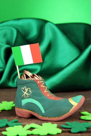 Saint Patrick day boot with gold coins and clover leaves on green background photo
