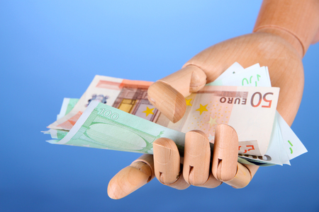 economise: Money in wooden hand, on color background Stock Photo