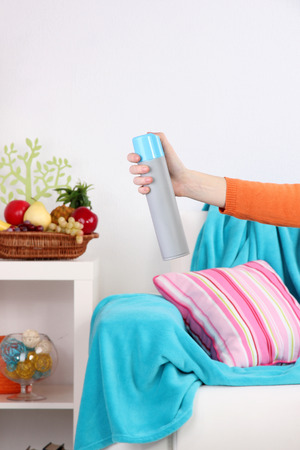 Sprayed air freshener in hand on home interior background photo