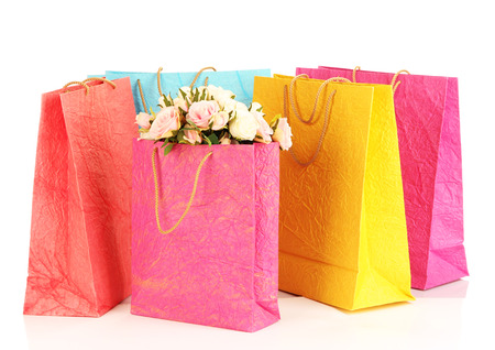 Colorful shopping bags and flowers, isolated on white photo