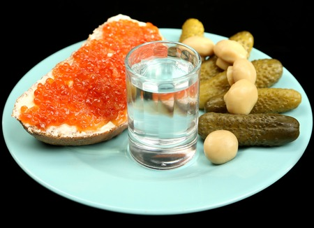 Composition with glass of vodka and snacks on color plate, isolated on black photo