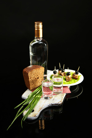 Composition with bottle of vodka, snacks with salted fish, green onion and glass on wooden board, isolated on black photo