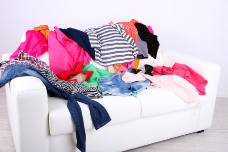 Messy colorful clothing on white sofa on white wall background photo